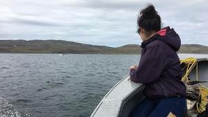 Une femme inuite sur un bateau regarde au large