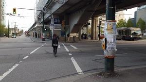 Une femme marche près du secteur dans l'est de Vancouver où deux femmes ont été attaquées, et une troisième, agressée sexuellement le 26 avril 2017.