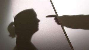 Une ombre de profil de femme et l'ombre d'un doigt qui pointe.