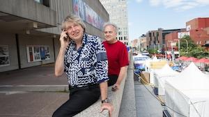 Alain Simard avec un téléphone cellulaire à l'oreille devant André Ménard au centre-ville de Montréal.