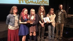 Entourées des membres du jury, deux élèves du Collége Béliveau acceptent le Grand prix du jury 2017 au gala du 25e Festival des vidéastes du Manitoba, à Winnipeg.
