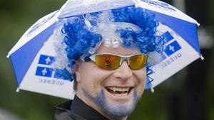 Homme portant une perruque surmontée d'un parapluie aux couleurs du Québec