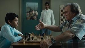 Depardieu tendant la main vers un jeune garçon originaire du Bengladesh, en face d'un jeu d'échecs.