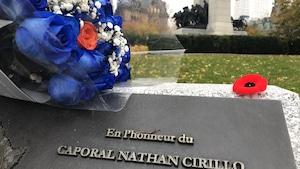Un bouquet de roses bleues est déposé sur la plaque, avec le monument en arrière-plan.
