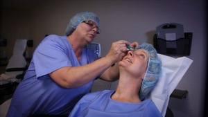 Une femme se fait mettre des gouttes dans une clinique ophtalmologique.