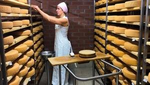 Léa Lehmann choisit une meule de fromage sur une tablette.
