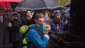 Des gens participent à une veillée funèbre sous la pluie, à Montréal.
