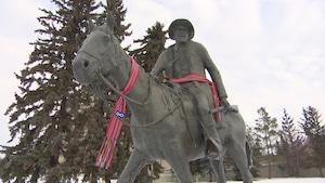 La statue de Gabriel Dumont revêt deux ceintures fléchées aux insignes métis.