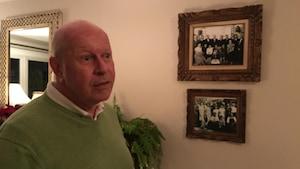 Gaétan Duguay dans sa maison, devant des photos de famille