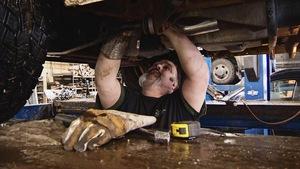 Un garagiste travaille sous une voiture surélevée.