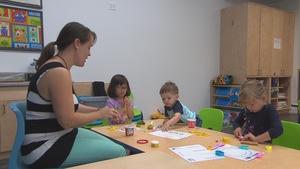 Une éducatrice en garderie accompagnée de trois enfants.