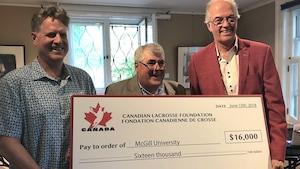 L'entraîneur Tim Murdoch, Jim Calder (Fédération canadienne de crosse) et Marc Gélinas (McGill) posent avec le chèque de 16 000 $ de la Fédération.