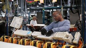 Un homme assemble les pièces d'un véhicule dans une usine de General Motors, au Michigan.