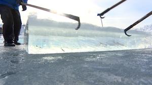 Un bloc de glace retiré d'un cours d'eau avec trois pinces à glace.