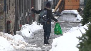 Une femme marche sur le trottoir.
