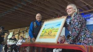 Un homme et une femme posent, tenant une aquarelle arborant un buffle dans une salle de conférence.