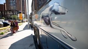 Le logo de la compagnie de transport Greyhound sur un autocar stationné au bord de la route en milieu urbain.
