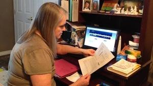 Devant son ordinateur, Elaine Wiebe tient son billet pour un trajet en autocar avec la compagnie Greyhound.