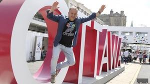 Guy Laflamme saute d'une lettre géante en forme de O, les bras dans les airs. Il est écrit Ottawa en lettres géantes.