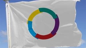 Le drapeau de l'organisation internationale de la francophonie flotte au vent sous un ciel bleu.