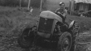 Photo d'époque d'Armand Blais de Hearst qui conduit son premier tracteur, un Ford Ferguson.