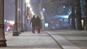 Un couple déambule sur le trottoir enneigé par un soir de novembre.