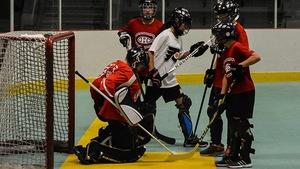 Des jeunes jouent au hockey dek.