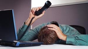 Un homme pose sa tête sur son bureau, le téléphone à la main.
