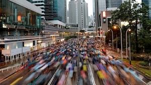 Des gens munis de parapluies défilent dans une rue.
