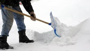 Un homme retire de la neige
