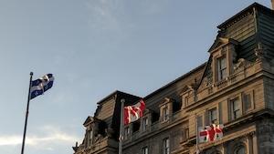 Les drapeaux du Québec, du Canada et de la Ville de Montréal flottent près de l'hôtel de ville de la métropole québécoise.