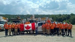 Un groupe de 25 hommes, certains tenant un gros drapeau canadien, posent pour une photo devant des camions.