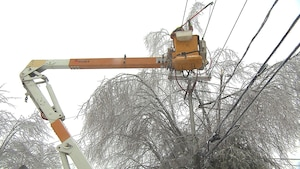 Un homme au sommet d'une grue répare des fils électriques endommagés par le verglas.
