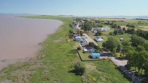 On voit du haut des airs les maisons et fermes de l'île aux Grues, en été, avec le fleuve Saint-Laurent en arrière-plan.