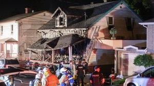 Une maison noircie par le feu, derrière un contingent de pompiers et de policiers, la nuit