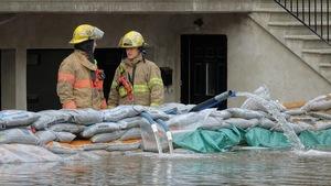 Deux pompiers de Montréal devant un garage où de l'eau est pompée