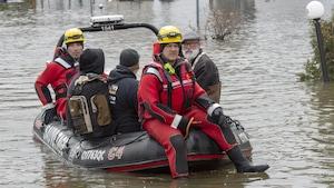 Des membres des services d'urgence transportent des citoyens à bord d'un navire.