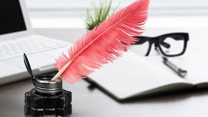 Une plume dans un encrier posé devant un ordinateur, un cahier et des lunettes.