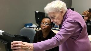 Une aînée aide une femme assise à l'ordinateur.