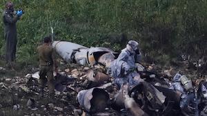 Des membres des forces de sécurité israéliennes examinent les restes de l'appareil de type F-16 qui s'est écrasé.