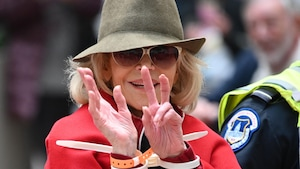 La femme porte un chapeau et montre ses poignets avec des menottes blanches.