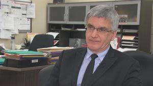 Un homme en complet assis devant un bureau lors d'une entrevue à la caméra de Radio-Canada.
