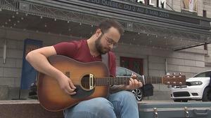 Jeffrey Piton avec sa guitare sur les marches devant le Palais Montcalm à Québec