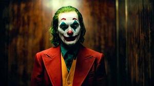 Un homme vêtu d'un veston rouge a le visage maquillé à la manière d'un clown. Ses cheveux sont teints en vert.