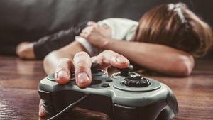 Une personne allongée sur le ventre, la tête dans le creux du coude et, en gros plan, une main posée sur une console de jeux vidéo.