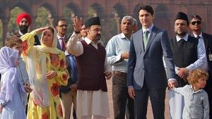 Justin Trudeau et sa famille sont entourés d'Indiens qui leur font visiter un site.