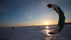 Un amateur de kitesurf déploie sa voile.