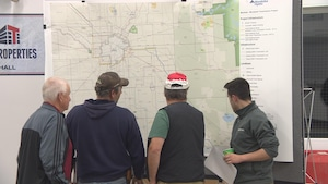 Des participants à l'audience publique de La Broquerie sur la ligne de transmission Manitoba-Minnesota consultent la carte du tracé.