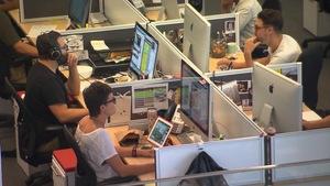 Des journalistes devant des écrans d'ordinateur à leur bureau de travail.