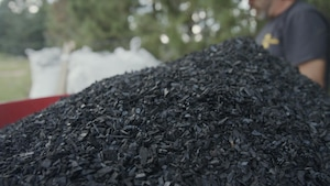 Un tas de grosses pépites de biochar avant d'être dispersé dans un champ agricole.